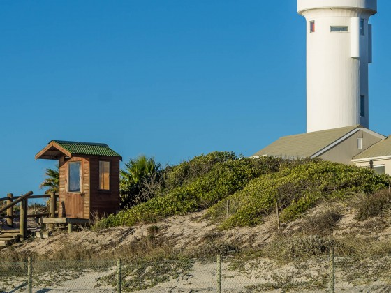 Woodbridge Island Lighthouse with security house on the beach